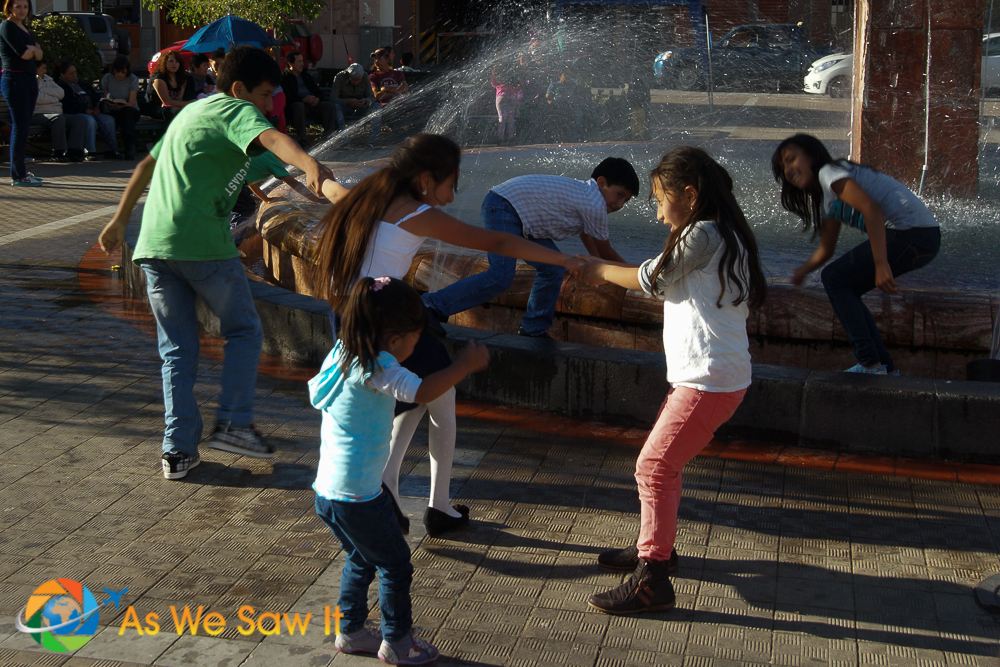 Children playing in a fountain on one of Cuenca's town squares.