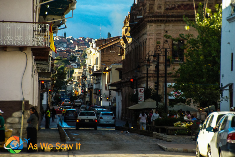 Cars drive down a Cuenca street that is full of apartments