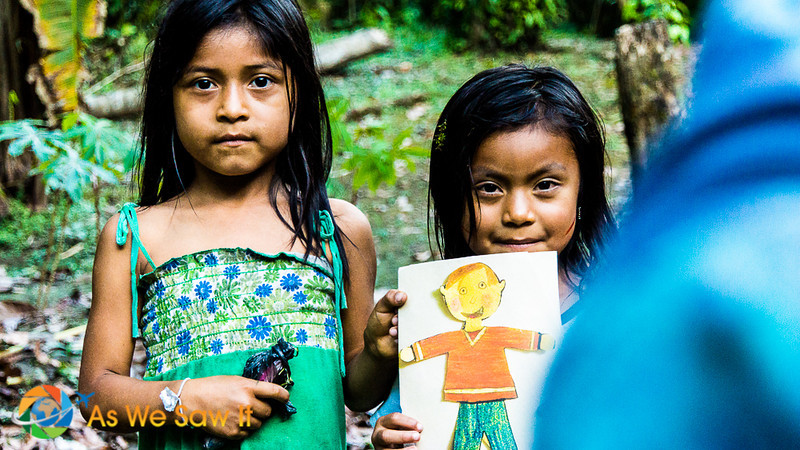 Two girls show us a cutout picture that they colored